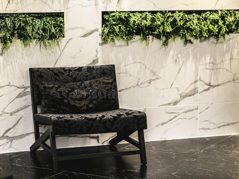 Sedia d'annata del bracciolo in salone interno con il marmo della parete per lo spazio della copia Interiore minimo fotografia stock