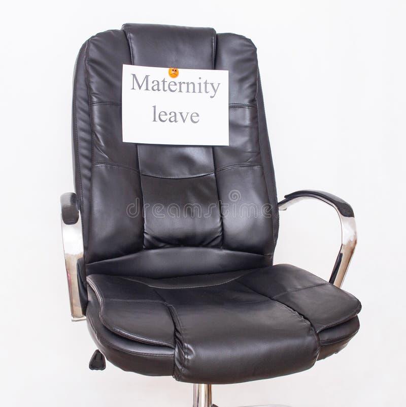 Sedia di cuoio dell'ufficio su cui il congedo di maternità dell'iscrizione Concetto e dikret di congedi parentali nel posto di la immagine stock
