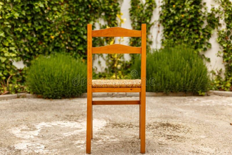 Sedia di legno e di vimini su un patio fotografia stock libera da diritti