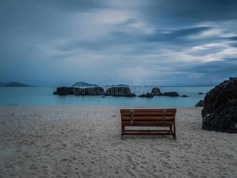 Sedia di legno sola sulla spiaggia dopo pioggia immagini stock