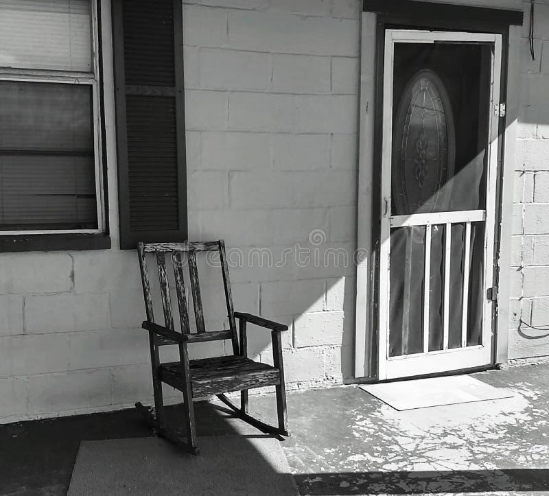 Sedia di oscillazione sul portico anteriore immagini stock libere da diritti