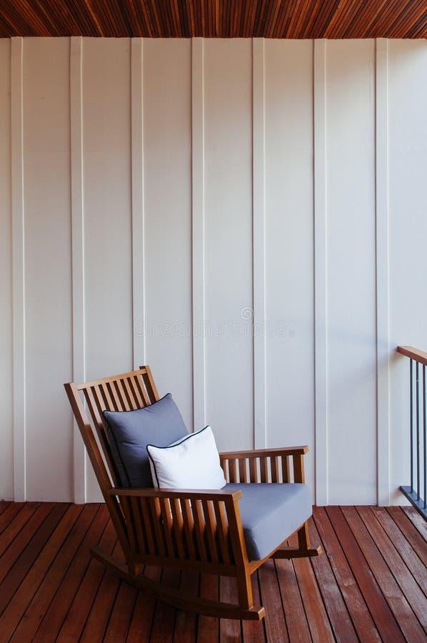 Sedia di oscillazione di Woooden al balcone di stile contemporaneo con evenin fotografia stock
