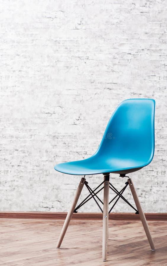 Sedia di plastica blu moderna in una stanza vuota con il pavimento di legno sul fondo grigio del muro di mattoni fotografia stock libera da diritti