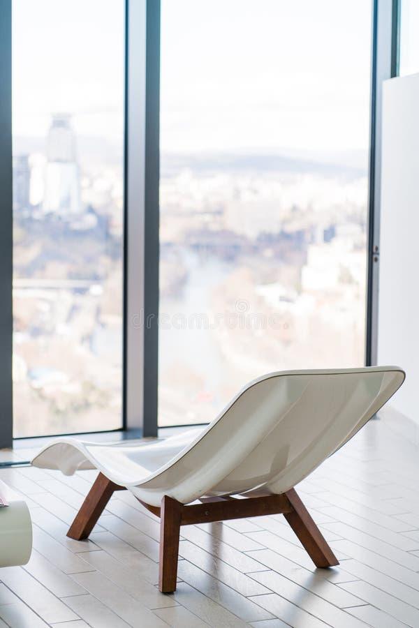 Sedia di salotto bianca vuota dentro di stanza piastrellata vicino alla piscina Nessuno nella stanza della stazione termale Sdrai immagine stock libera da diritti