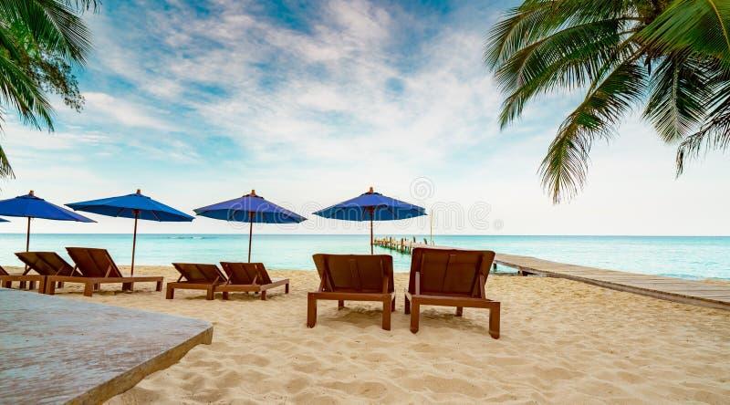 Sedia di spiaggia ed ombrello di spiaggia di legno alla spiaggia di sabbia della località di soggiorno accanto al ponte Viaggio d fotografia stock libera da diritti