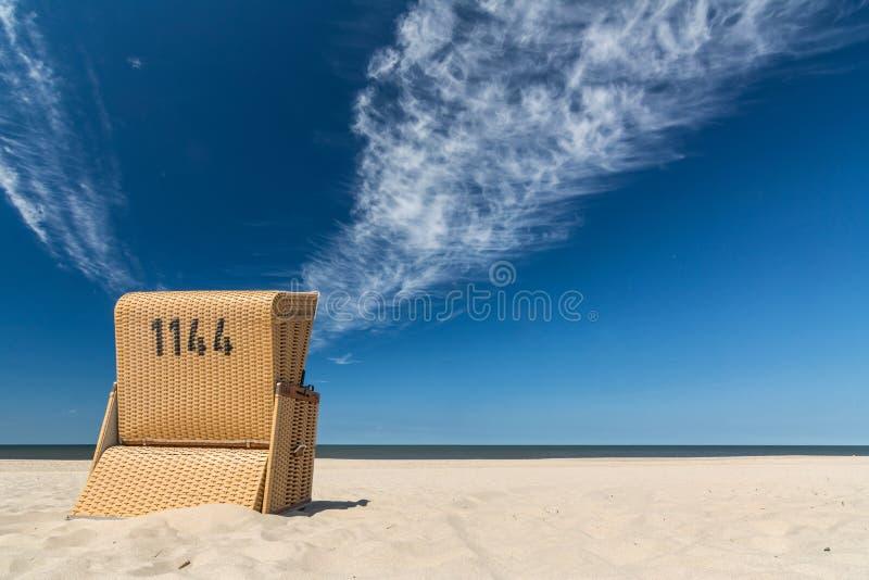 Sedia di spiaggia sola che affronta l'oceano sotto il bello cielo blu fotografie stock