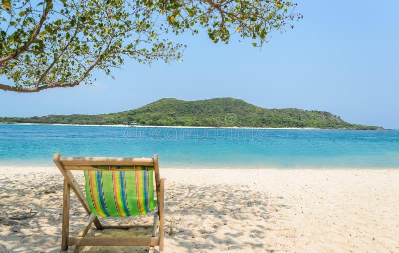 Sedia di spiaggia sulla sabbia con l'isola fotografia stock libera da diritti