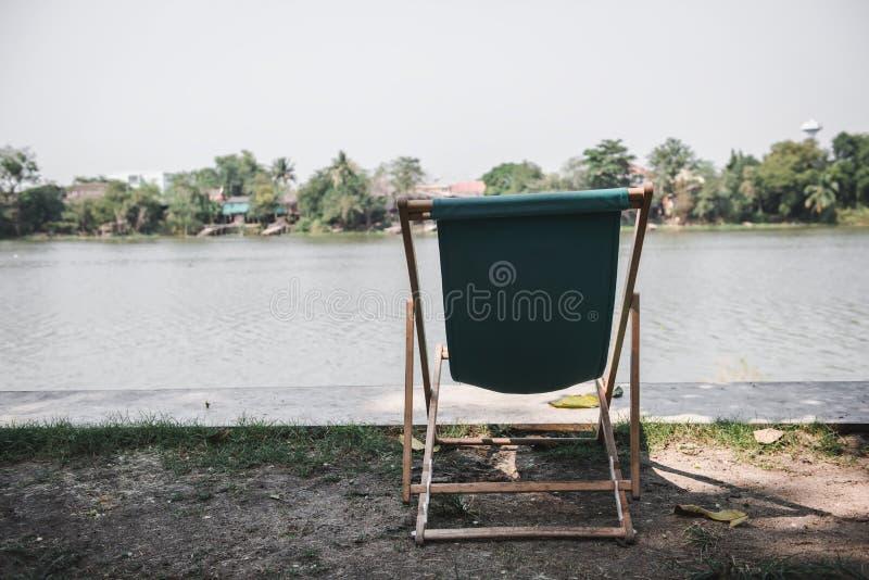 Sedia di spiaggia vuota in giardino all'aperto accanto al fiume, concetto solo fotografia stock libera da diritti