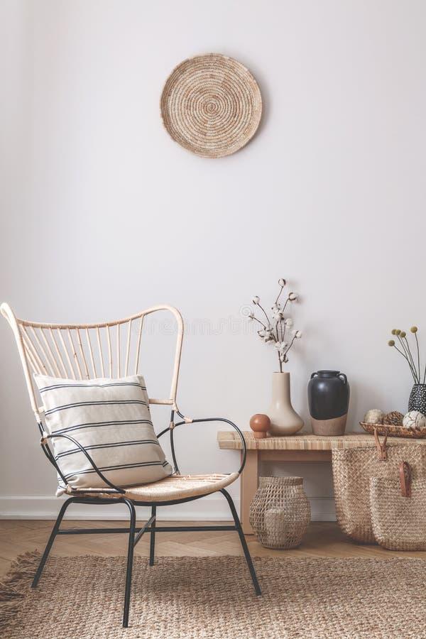Sedia di vimini con il cuscino a strisce su accanto alla tavola di legno in pieno degli accessori quali il vaso, i fiori e le can fotografie stock