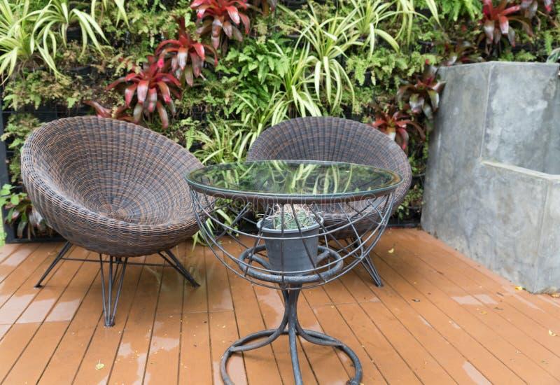 sedia di vimini e scrittorio del rattan sul patio immagine stock