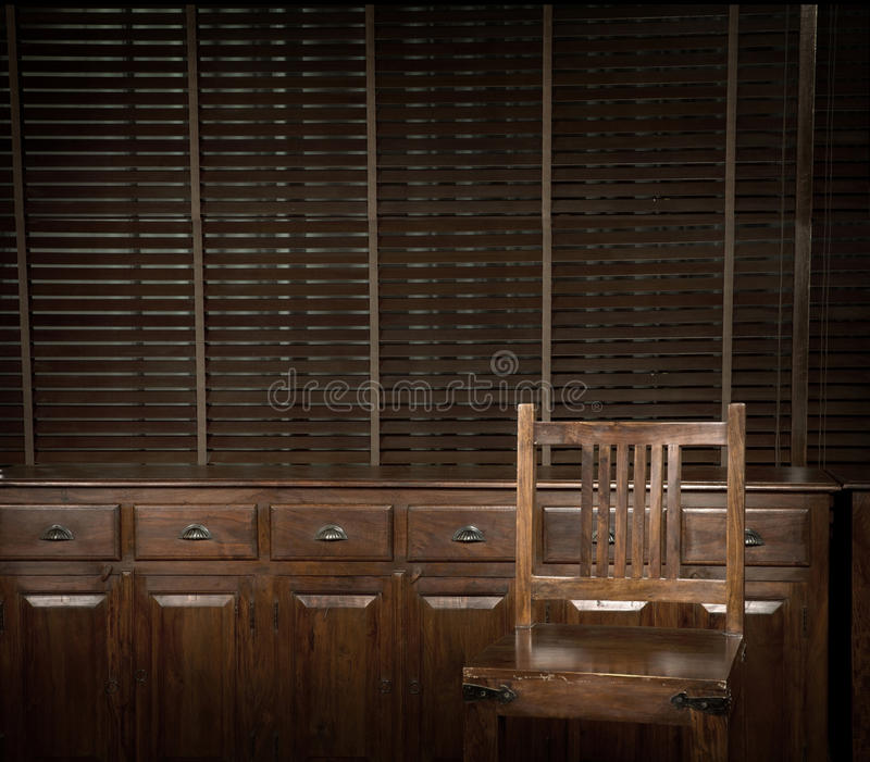 Sedia e cassettone di legno con i ciechi come fondo immagini stock libere da diritti
