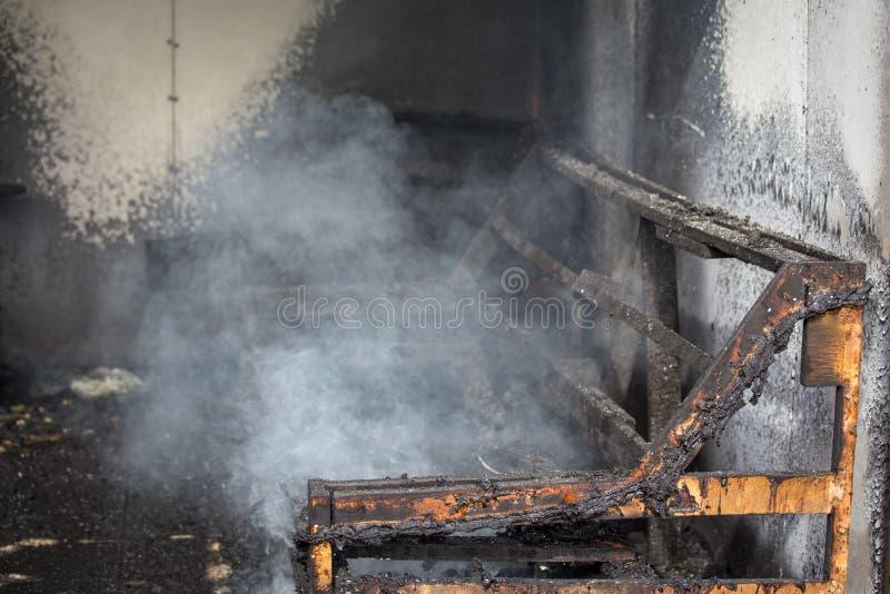 Sedia e mobilia nella sala dopo bruciato nella scena dell'ustione di incendio doloso fotografia stock