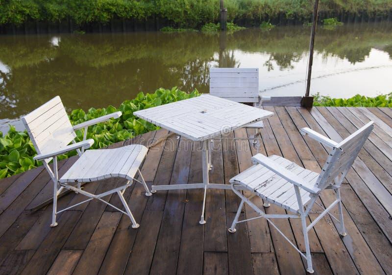 Sedia e tavola di giardino con la riva del fiume fotografia stock libera da diritti