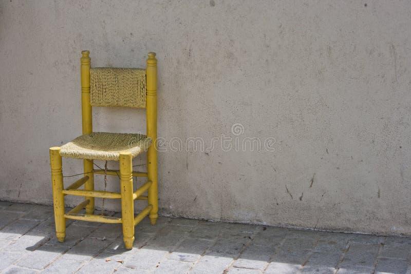 Sedia gialla contro il muro di mattoni a Costantinopoli fotografie stock