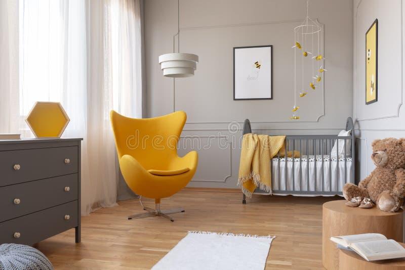 Sedia gialla d'avanguardia dell'uovo in scuola materna grigia elegante con la greppia ed i manifesti di legno sulla parete fotografia stock libera da diritti