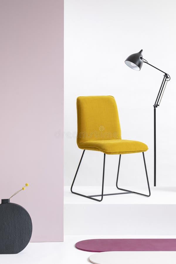 Sedia gialla del velluto alla moda accanto alla lampada nera industriale alta nell'interno bianco fotografia stock libera da diritti