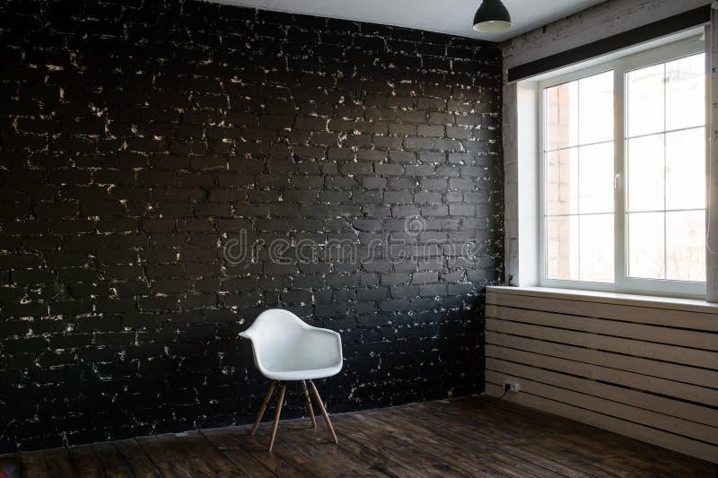 Sedia moderna bianca e fondo nero del mattone Stile del sottotetto Sedia e stanza minime Sedia di eleganza fotografie stock