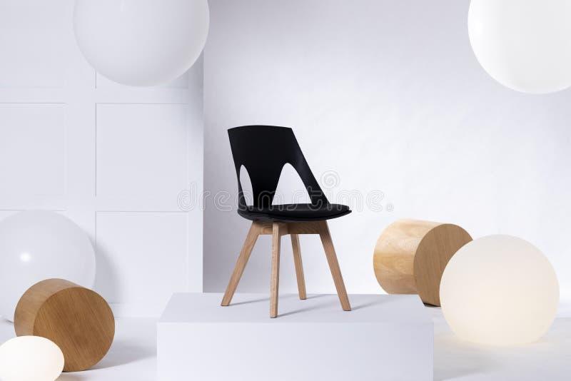 Sedia nera alla moda sulla piattaforma bianca in sala d'esposizione luminosa interna con i grandi palloni ed i blocchi di legno fotografie stock