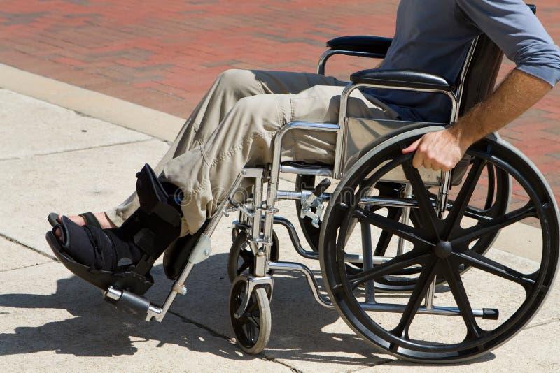 Sedia a rotelle danneggiata dell'uomo fotografia stock