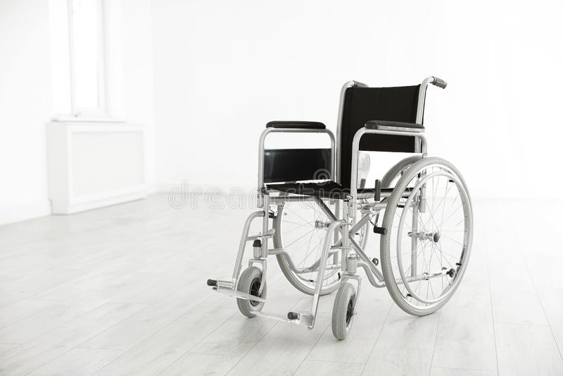 Sedia a rotelle moderna nella stanza vuota Attrezzatura medica immagini stock