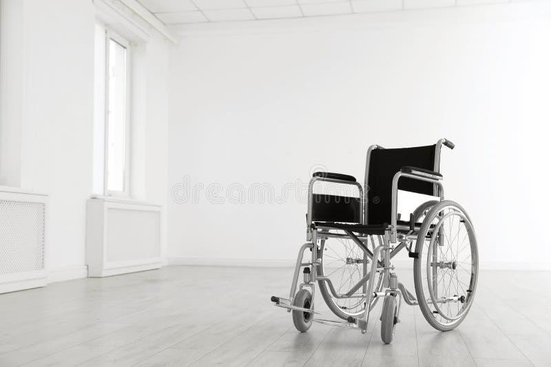 Sedia a rotelle moderna nella stanza vuota Attrezzatura medica fotografie stock