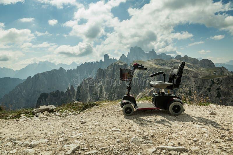 Sedia a rotelle motorizzata per la gente eliminabile, carrozzini elettrici mobili sulla montagna, dolomia, Italia fotografia stock libera da diritti