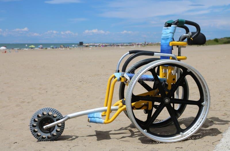 Sedia a rotelle speciale da potere muoversi sulla sabbia di estate immagini stock