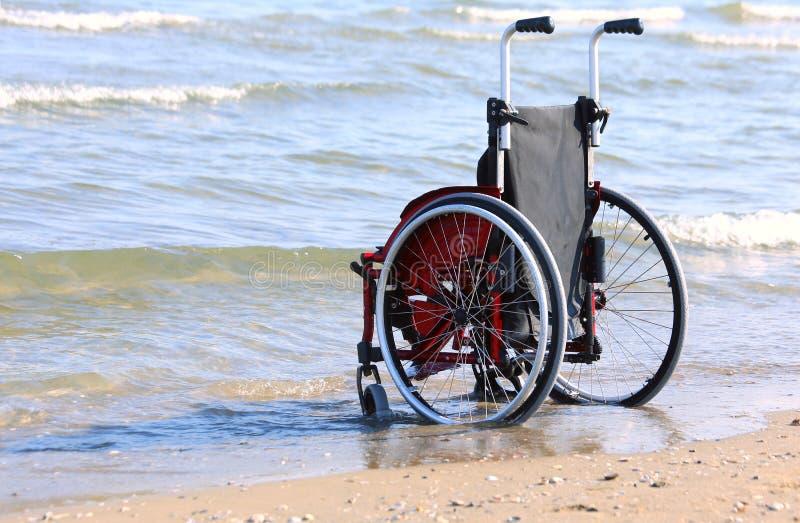 Sedia a rotelle sulla riva dal mare fotografie stock