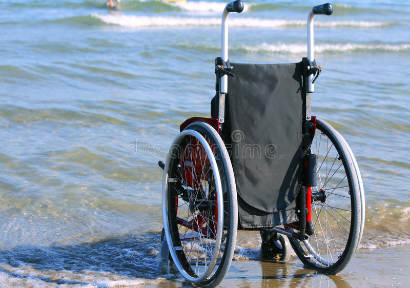 Sedia a rotelle sulla riva dal mare un giorno di estate soleggiato caldo fotografia stock