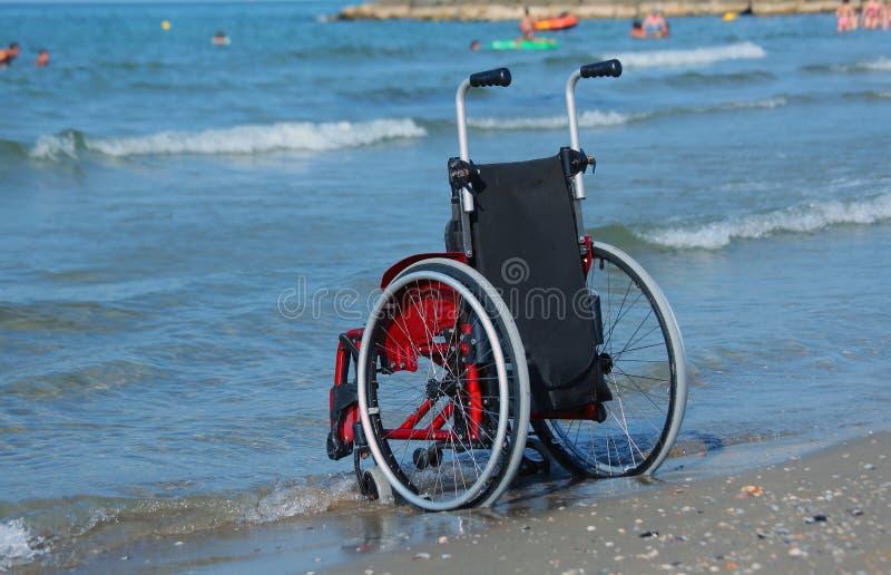 Sedia a rotelle sulla riva dal mare un giorno di estate soleggiato caldo fotografie stock