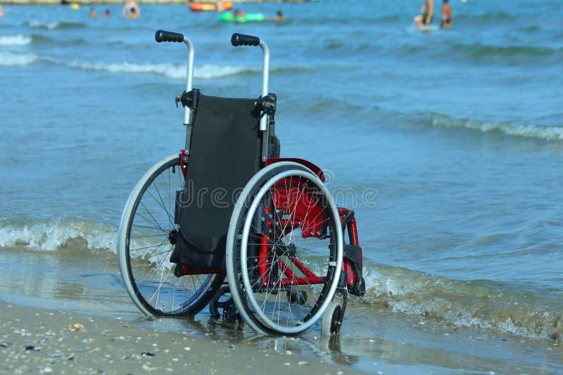 Sedia a rotelle sulla riva dal mare un giorno soleggiato immagine stock libera da diritti