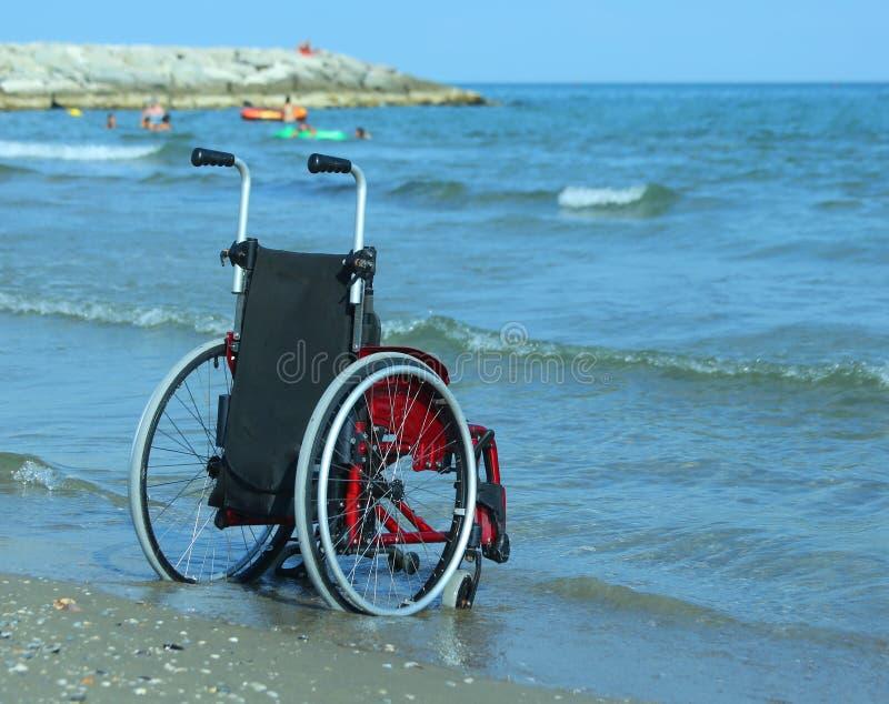 Sedia a rotelle sulla riva dall'oceano un giorno di estate soleggiato caldo immagini stock libere da diritti