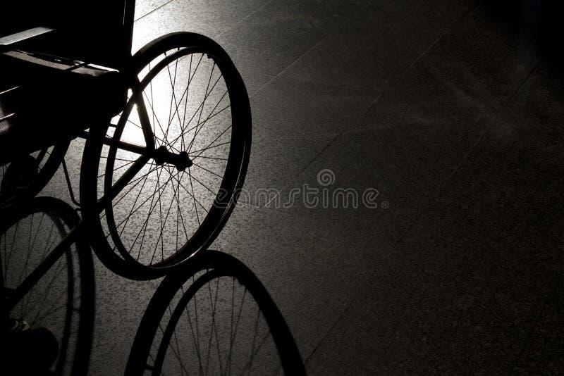 Sedia a rotelle vuota del primo piano su fondo scuro fotografia stock