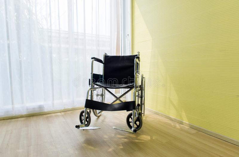 Sedia a rotelle vuota per il paziente nella sala all'ospedale fotografia stock