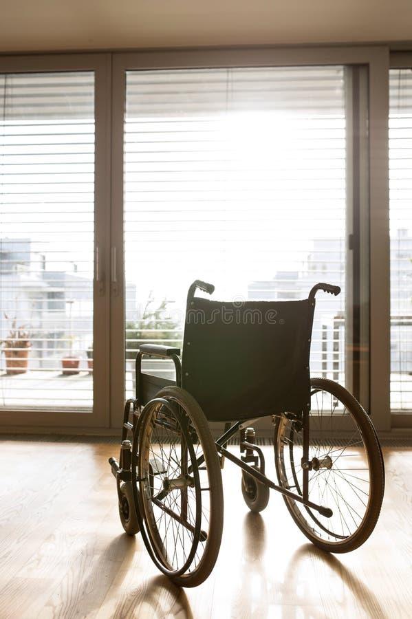 Sedia a rotelle vuota in salone accanto allo strato fotografia stock