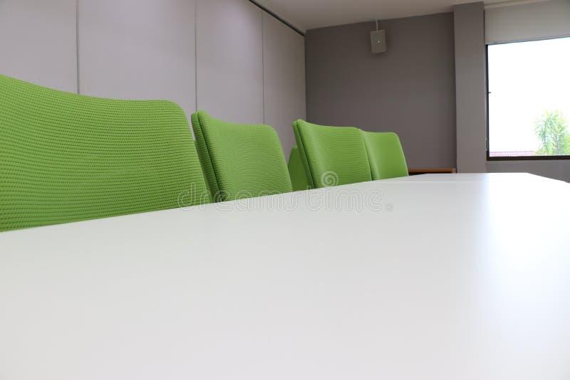 Sedia verde con la tavola bianca dentro la sala riunioni fotografia stock libera da diritti