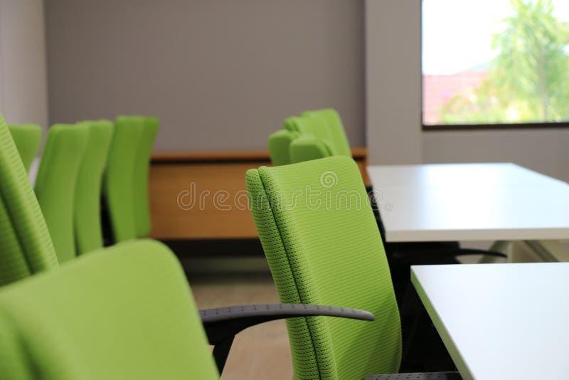 Sedia verde con la tavola bianca dentro la sala riunioni immagine stock libera da diritti