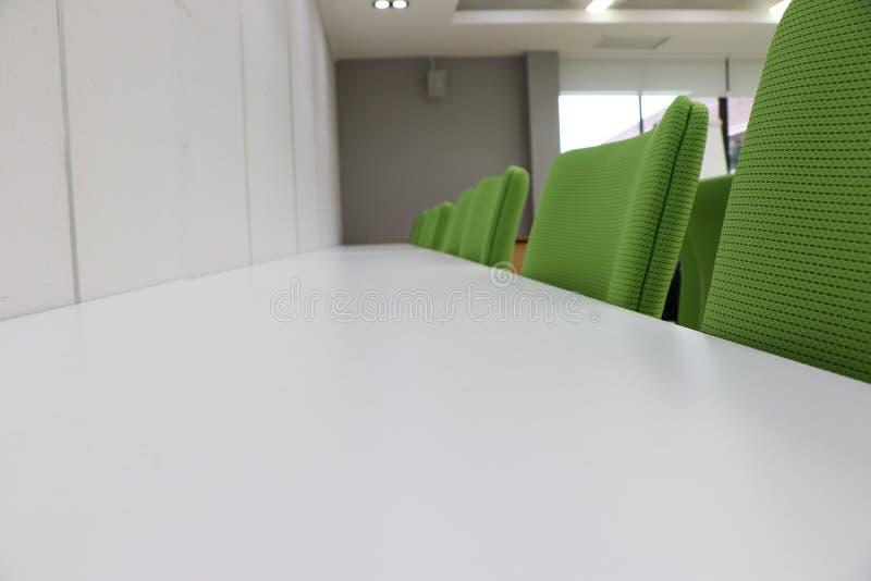 Sedia verde dentro una sala riunioni fotografie stock