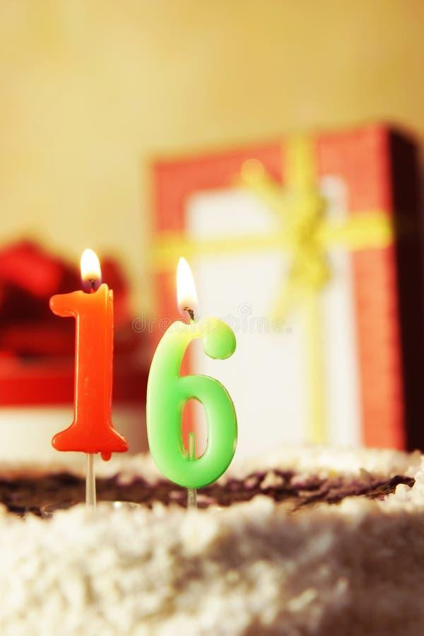 Sedici anni Torta di compleanno con le candele burning fotografie stock libere da diritti