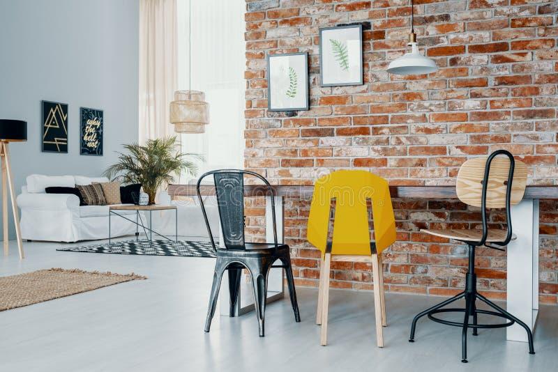 Sedie al tavolo da pranzo contro il muro di mattoni rosso con i manifesti nell'interno dello spazio aperto con il sofà bianco Fot immagini stock