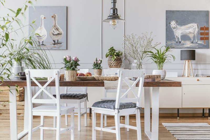 Sedie bianche alla tavola di legno con i fiori nell'interno eclettico della sala da pranzo con i manifesti Foto reale fotografia stock libera da diritti