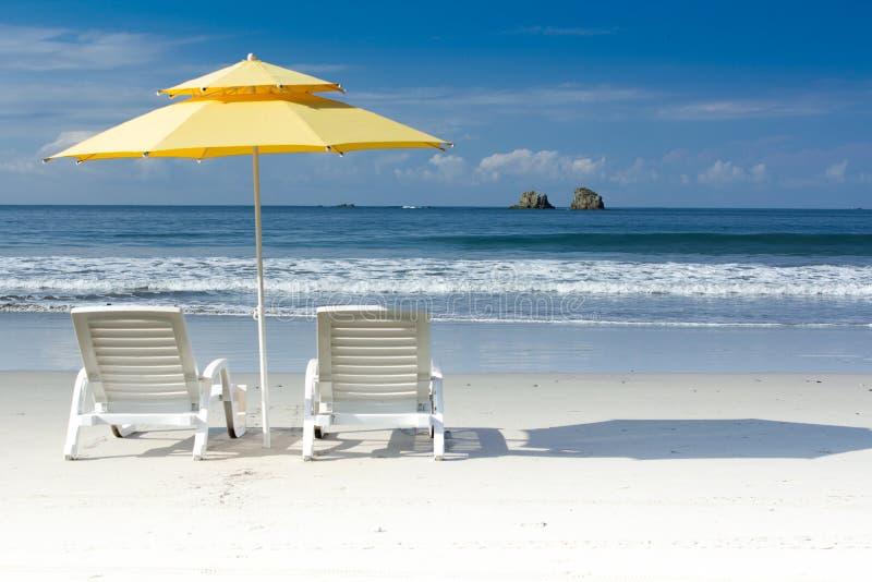 2 sedie bianche ed ombrello giallo sulla spiaggia tropicale immagine stock