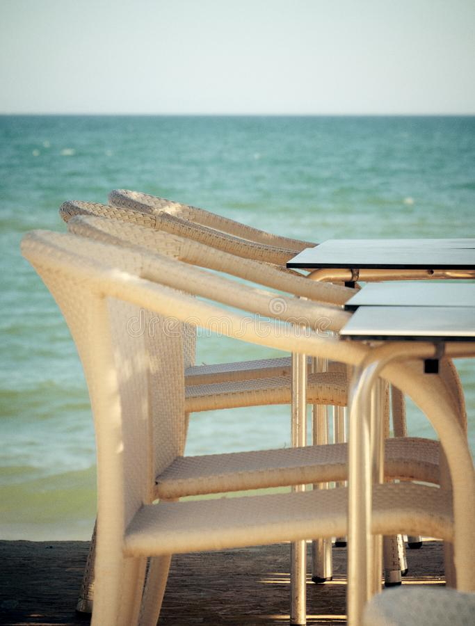 Sedie bianche nella barra della spiaggia fotografia stock