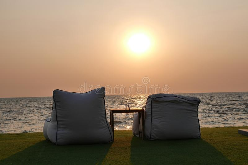 Sedie che affrontano tramonto sopra sopra il golfo del Siam fotografia stock