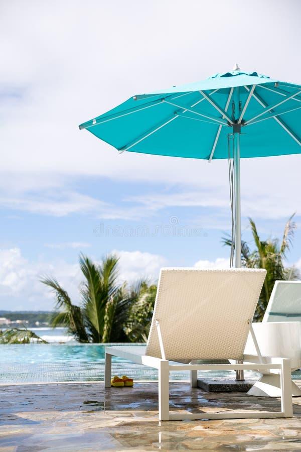 Sedie con il parasole blu il giorno soleggiato fotografie stock