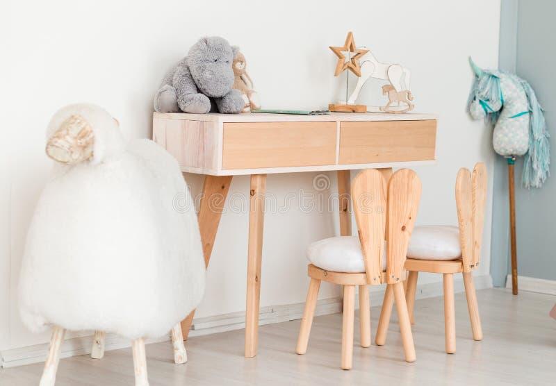 2 sedie con le orecchie del coniglietto nella stanza dei bambini, in una tavola con i giocattoli ed in una grande pecora fotografia stock