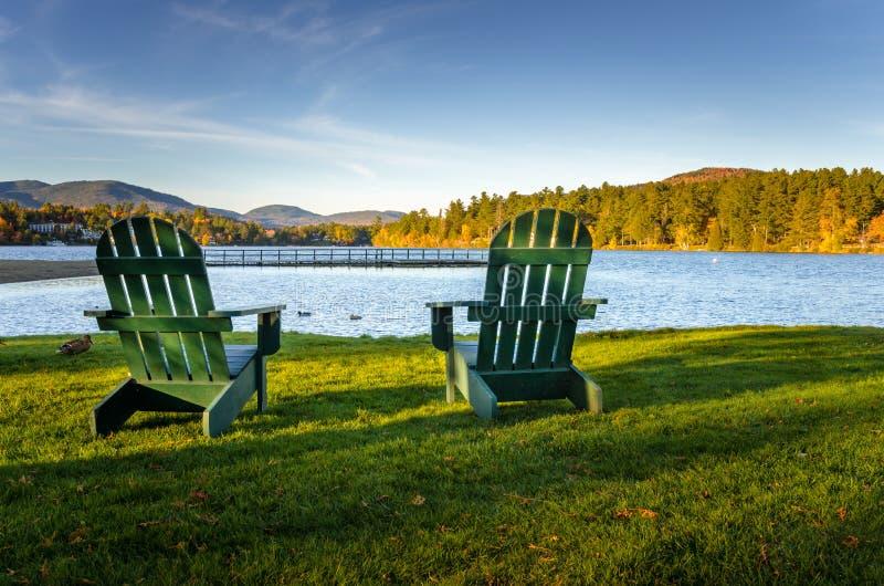 Sedie di Adirondack davanti ad un lago fotografie stock libere da diritti