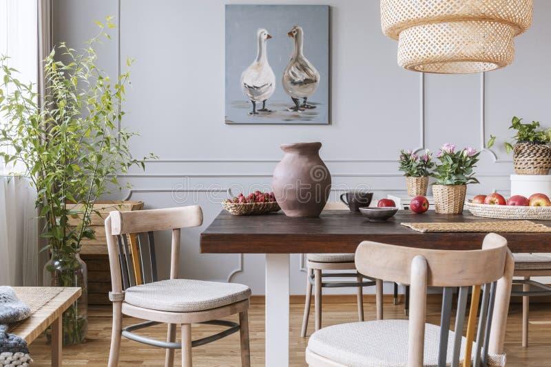 Sedie di legno alla tavola con i fiori nell'interno naturale della sala da pranzo con il manifesto e la lampada Foto reale fotografia stock libera da diritti