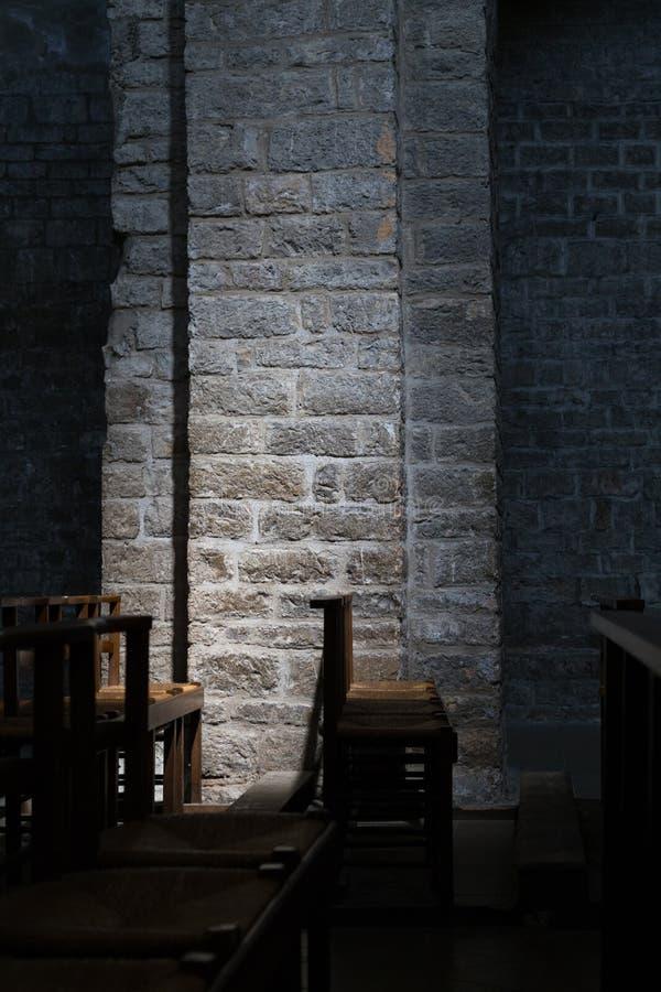Sedie di legno in una chiesa scura, illuminazione sottile sulla parete di pietra fotografie stock libere da diritti