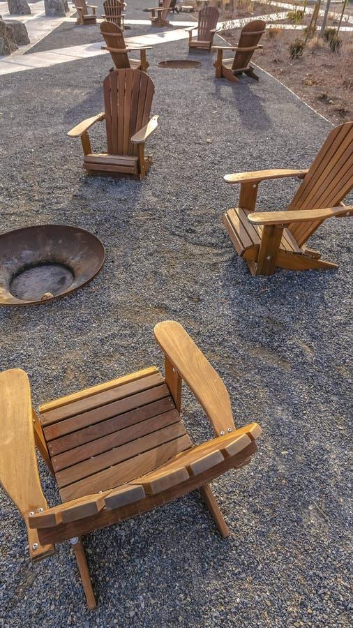 Sedie di legno verticali di Brown intorno ad un pozzo del fuoco ad un parco un giorno soleggiato fotografie stock